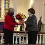 Choir member Barbara Carroll presents a bouquet to Chris on behalf of St. Gregory's Choir.