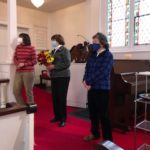 Three members of the choir listen as Chris Psolka is regaled for her music ministry at Christ Church